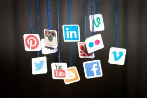 Social media icons hanging on blue twine.