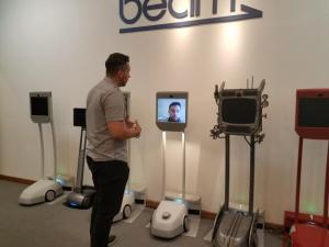 Man looking at telepresence machines.