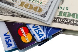 Tambov, Russian Federation - May 25, 2014: Dollars and credit cards with the logos of Visa and Mastercard. Visa and Mastercard are a two biggest credit card companies in the world.
