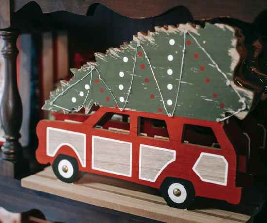 decorative christmas vehicle with fir tree on shelf