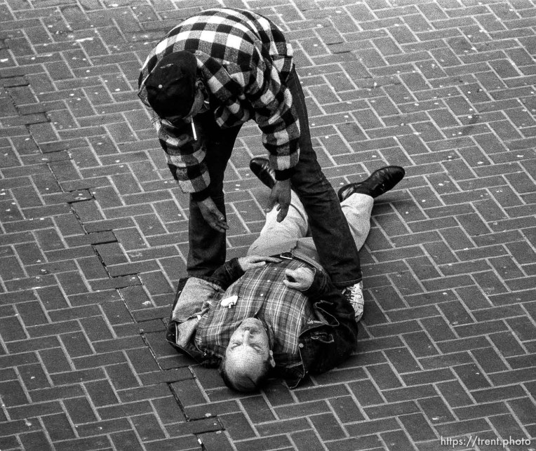 Man on ground being offered assistance at 5th and Market St.