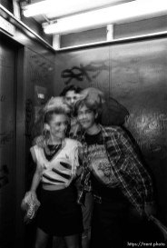 People in elevator posing.