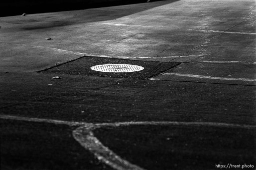 Manhole behind Alpha Beta at night.