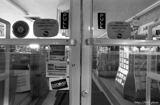 Store glass doors and stickers on Center Street at night.