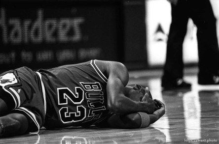 Michael Jordan on the ground holding his head at Jazz vs. Chicago basketball.