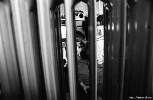 People living in the Hideaway Motel. Boy looking through space heater.