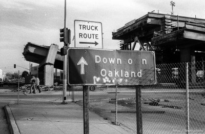 "Altered sign reading ""Down on Oakland"" in front of Ruins of the Nimitz Freeway, which collapsed in the 10/89 earthquake."