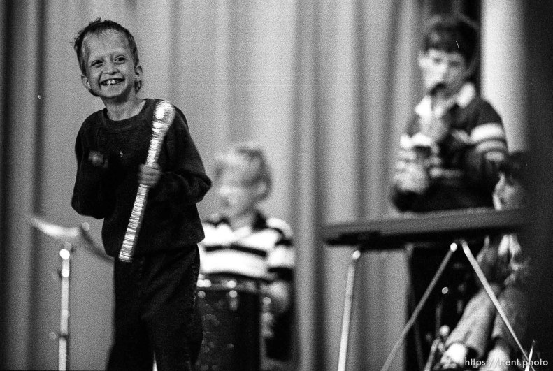 Boy with American flag at talent show for mentally disabled children.