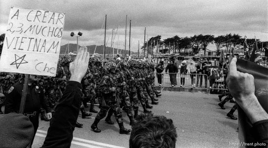 People harrass military troops at Gulf War celebration parade.