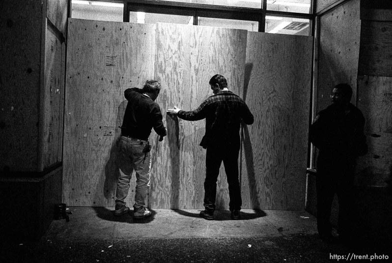 Men board up windows after riots along Telegraph Avenue.