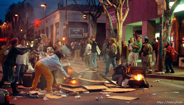 People starting fires in the street during riots and protests.