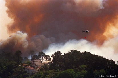 The Oakland Hills Fire threatens homes on Grizzly Peak while a helicopter makes water runs. The homes survived.