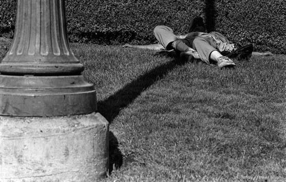 Man sleeping in shade of post.