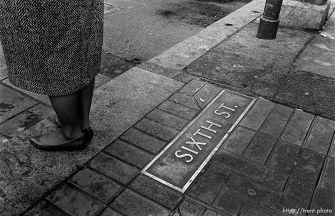 """Woman's feet and """"Sixth St"""" plaque on ground."""