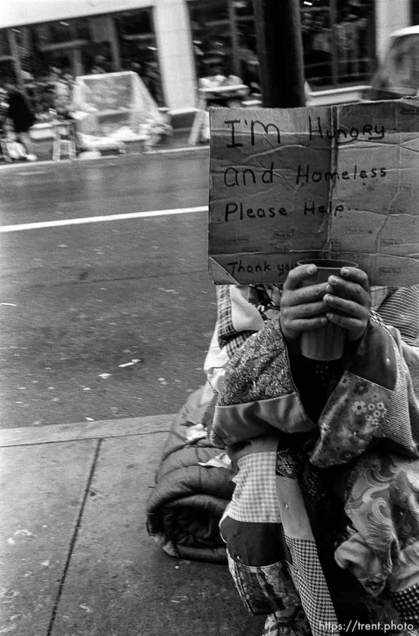 """Homeless person with """"I'm hungry and homeless please help"""" sign."""