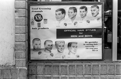"""""""Official Hair Styles for Men and Boys"""" sign in barbershop window."""