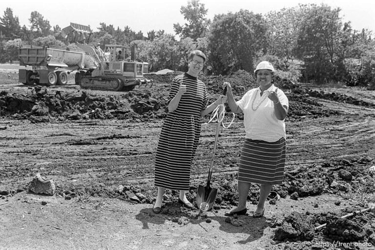 Women in a field with a shovel, giving the thumbs-up sign