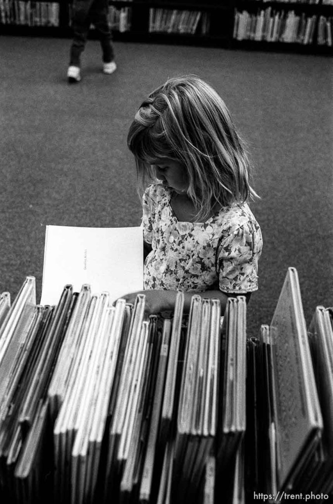 Girl in library looking at books at first day of kindergarten