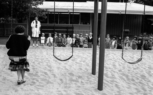 Teacher shows kids the proper way to swing at first day of kindergarten