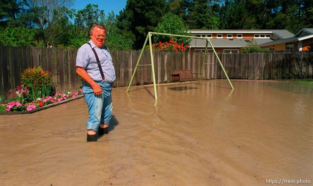 Man in his yard when at home flooded by broken water main.