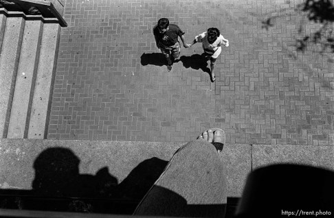 Trent feet and couple walking through plaza