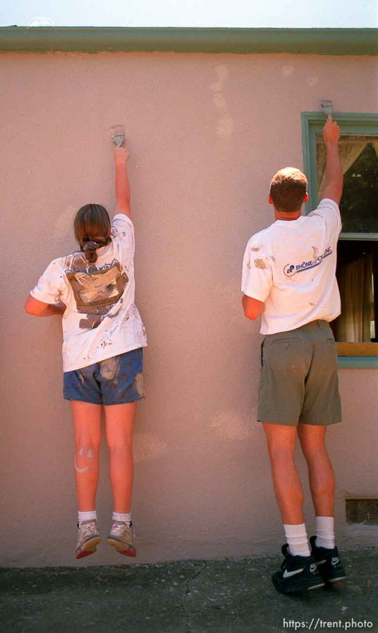 Girl jumping up while painting house