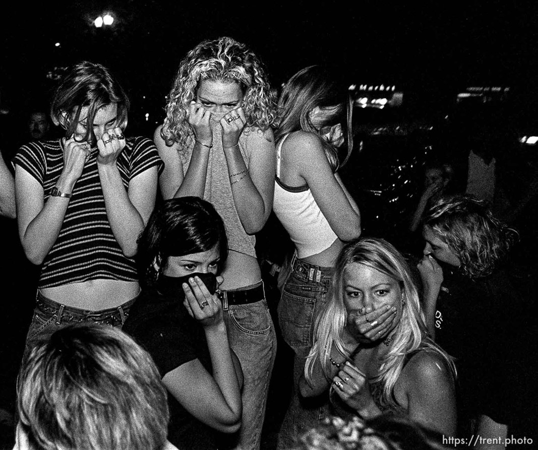 Girls cover their faces from police tear gas at riot that broke out during straightedge concert.