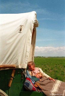 Sarah Dicken rests in her mother Shauna's arms. Sarah is sick with a 102 degree fever, as the Mormon Trail Wagon Train stops for lunch.