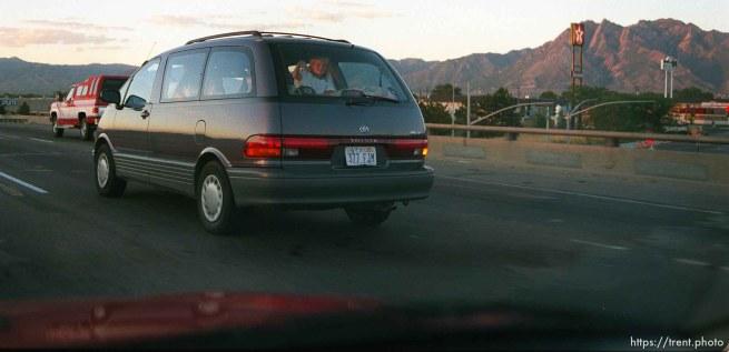 Little girl in back of van waving. Utah drivers.