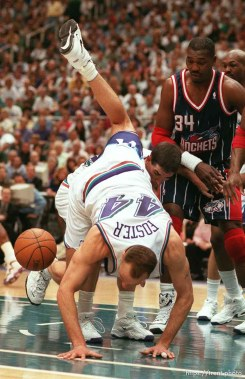Utah's Greg Foster goes over John Stockton trying to get a loose ball at Utah Jazz vs. Houston Rockets, game 5 of the 1st round, NBA Playoffs. Jazz won. Hakeem OIajuwon in the background (#34).