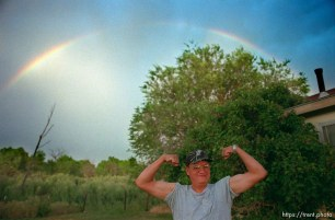 David Wopsock flexes his muscles under a rainbow.