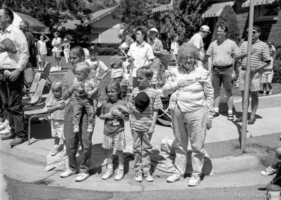 Parade watchers cover their hearts as the U.S. flag passes at the 4th of July parade on Main Street.