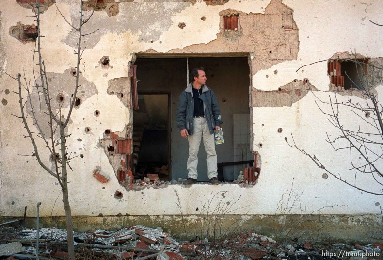 Naim Begiri in the ruins of his uncle's house, where he hid from Serb forces during the war.