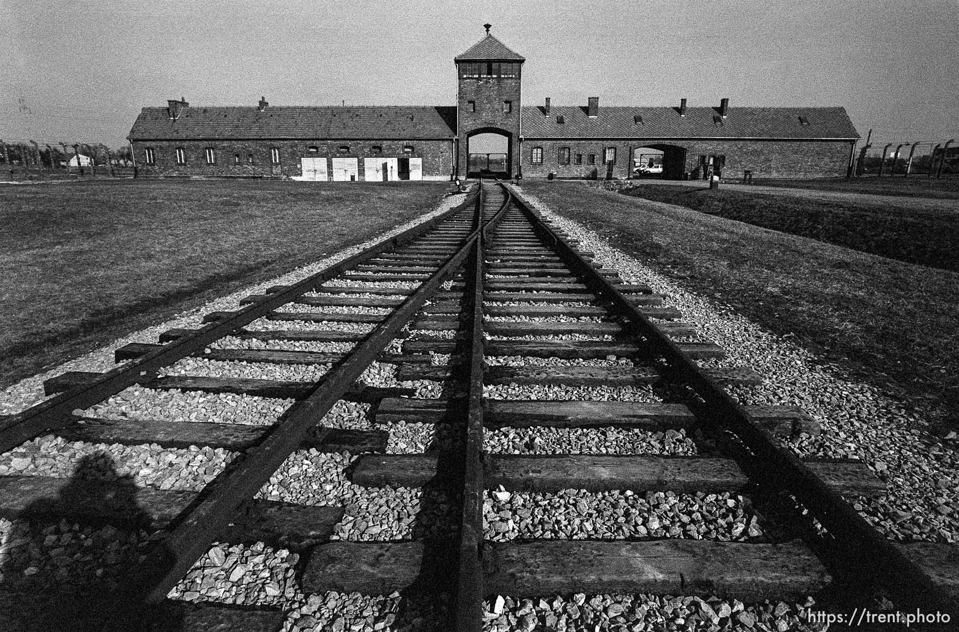 """Trent shadow, rails, and the """"Death Gate"""" at the Birkenau Concentration Camp."""