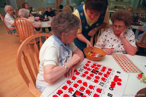 Mary Beth Wynder (center) hands out candy to Goldie Bagnell (left) while playing Bingo at Heritage Place, a senior home.