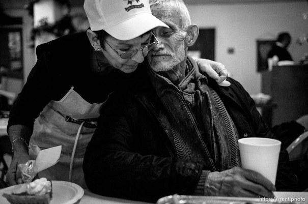 Volunteer Barbara Wilkinson gives Robert Carothers a hug Thanksgiving dinner at the Salt Lake City Mission.