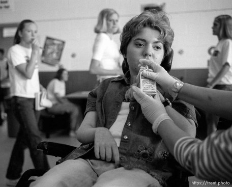 Suzanne Yelton, a special needs teacher assistant, feeds lunch to Michelle Salisbury.
