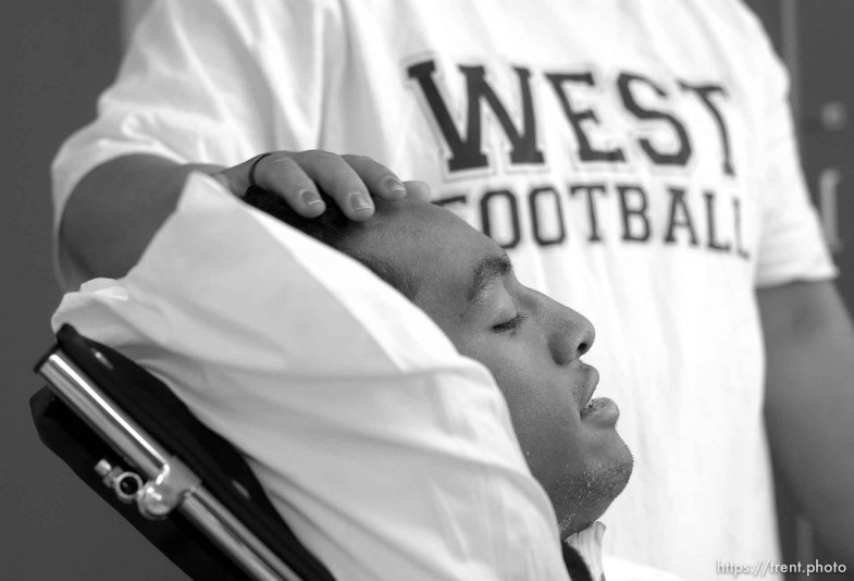 Una Taufa sits in a wheelchair while his sister Ola Taufa rubs his forehead. West High football player Una Taufa suffered a severe neck injury in a game two weeks ago and is partially paralyzed. He has begun the long and arduous rehabilitation process at LDS Hospital. . 09/27/2001, 11:33:50 AM