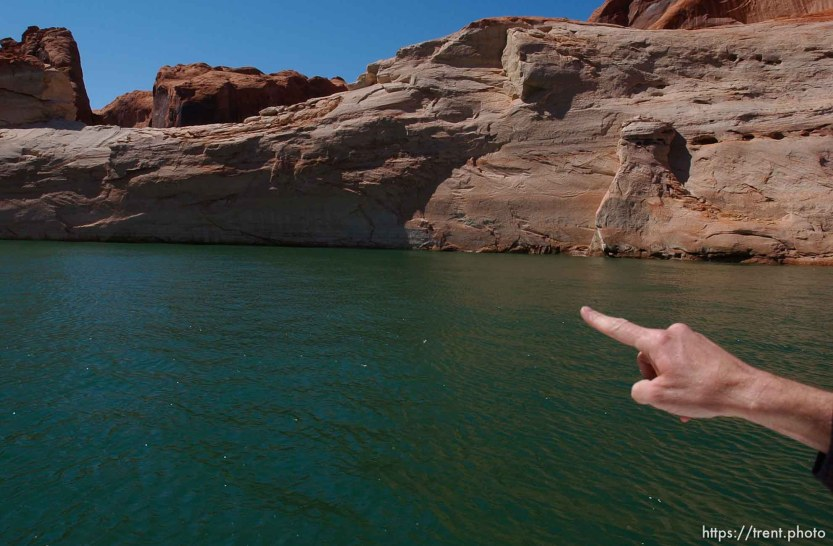 Richard Ingebretsen, founder and president of the Glen Canyon Institute, points out the top of the previously submerged Gregory Natural Bridge. He believes that if the lake drops another five feet, the arch will be above the lake's surface. Landmarks which had previously been submerged in Glen Canyon are now becoming visible with the lower water levels in Lake Powell.