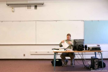 East Carbon High School math teacher Rex Jepson sifting through papers in his empty classroom. The small town of Sunnyside's East Carbon High School is being closed. The students will be transfered to Price's Carbon High School, a 25-minute bus ride away.