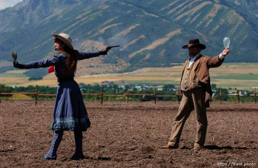 Famous western sharpshooter Annie Oakley (Marna Jean) uses a mirror to take aim at a balloon in her partner Frank Butler (Doug Davis)'s mouth during a Wild West Show that kicked off the Festival of the American West at Wellsville's American West Heritage Center.