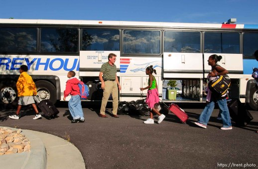 A family from New Orleans makes their way to a bus headed to Dallas and then Houston, Texas. About 100 of the 600 or so evacuees housed at Camp Williams boarded buses to Dallas, Texas Wednesday evening. From Dallas, they will make they way to a variety of locations and reunite with friends and family members.