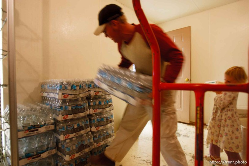Centennial Park - Ianthus Hammon loads bottled water into the large walk-in cooler at a community store in Centennial Park, Arizona. Young men from the fundamentalist community of Centennial Park serve work missions after they graduate high school. They work construction or other jobs, help the needy, and do volunteer work. ; 7.25.2006