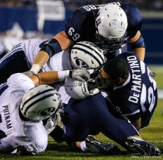 Trent Nelson | The Salt Lake Tribune BYU defensive lineman Matt Putnam (41) pulls off Joey DeMartino's helmet during the first half. Utah State vs. BYU college football in Logan Friday, October 1, 2010.