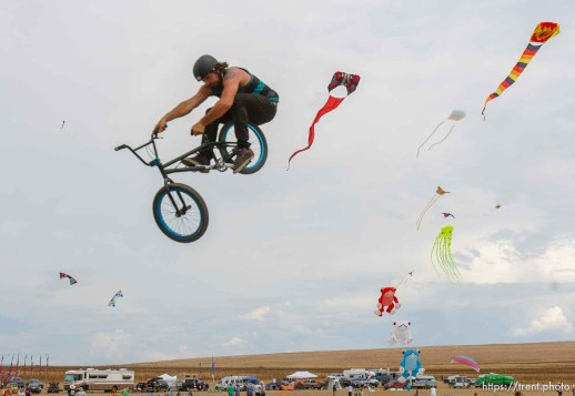 Trent Nelson | The Salt Lake Tribune Jonesy Fedderson shares the sky with a variety of kites during the Antelope Island Stampede, Saturday, August 31, 2013 at Antelope Island's White Rock Bay.