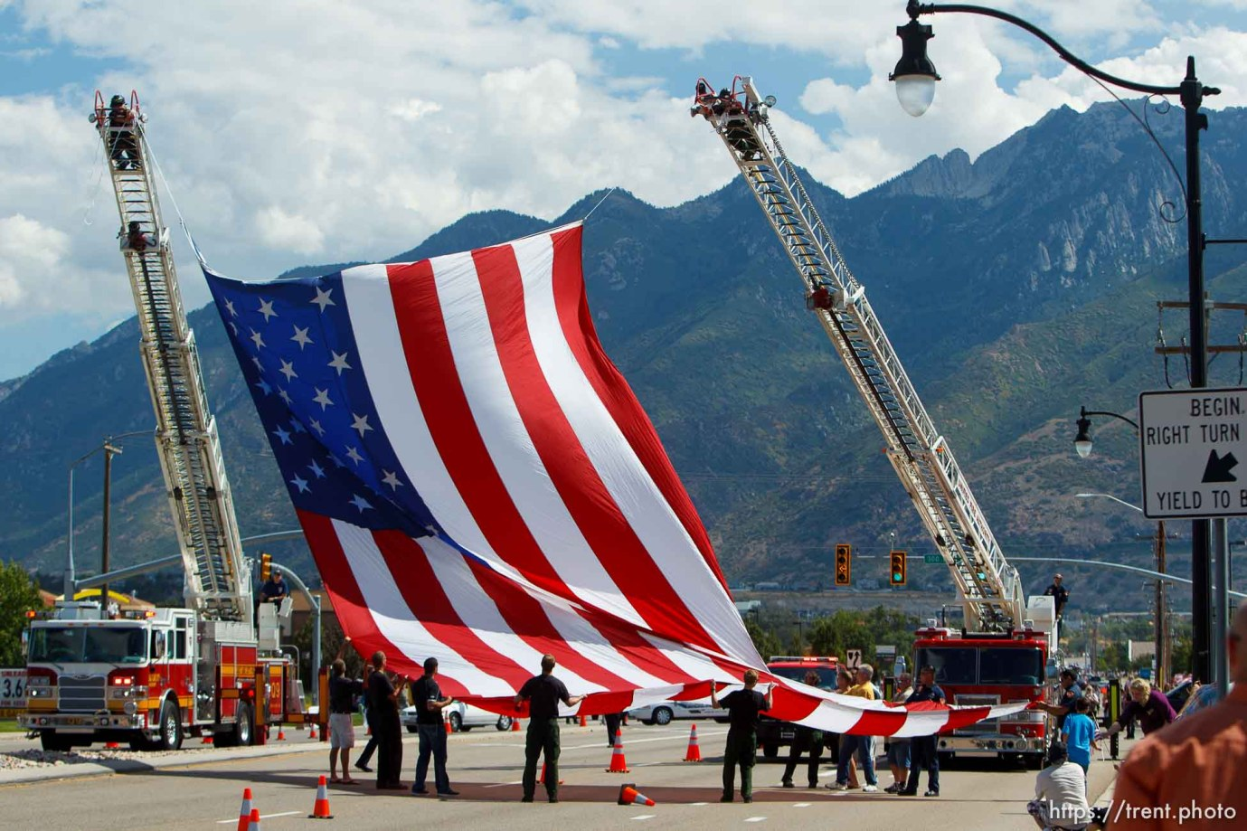 Trent Nelson | The Salt Lake Tribune Firefighters hoist a giant flag on 12300 South in preparation for the funeral procession for Sgt. Derek Johnson, the Draper police officer who was shot to death on Sunday morning, passes through Draper Friday, September 6, 2013.