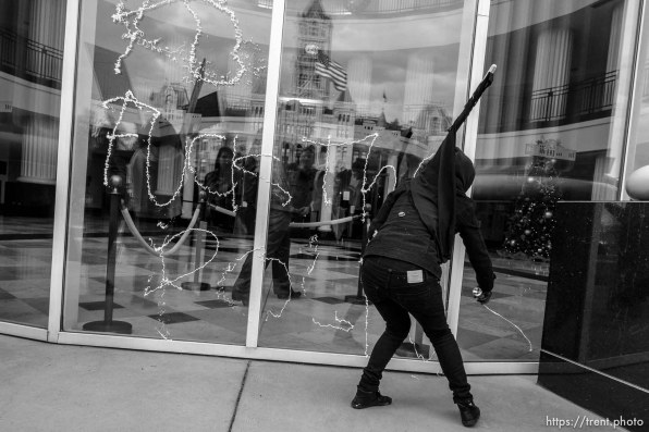 Trent Nelson | The Salt Lake Tribune A masked protester sprays silly string onto the windows of the Matheson Courthosue as approximately 350 people turned out for a rally to protest police brutality in Salt Lake City, Saturday November 29, 2014.