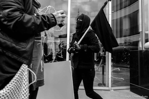 Trent Nelson | The Salt Lake Tribune A masked protester sprays silly string onto the windows of the Matheson Courthosue as approximately 200 people turned out for a rally to protest police brutality in Salt Lake City, Saturday November 29, 2014.