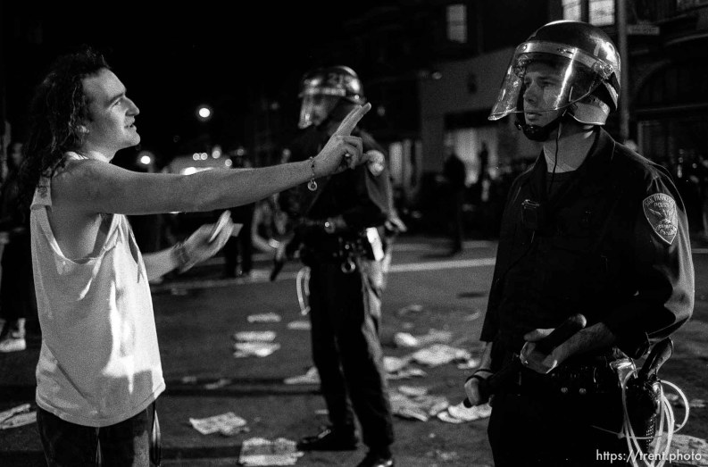 Man holds out peace sign to police officer at Gulf War protest.
