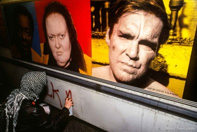 Gulf War protester spray-painting on bus with funny people sign.